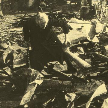 Alte Frau sucht in den Trümmern nach einem Luftangriff, 1942.jpg
